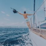 man hanging off of a sailboat
